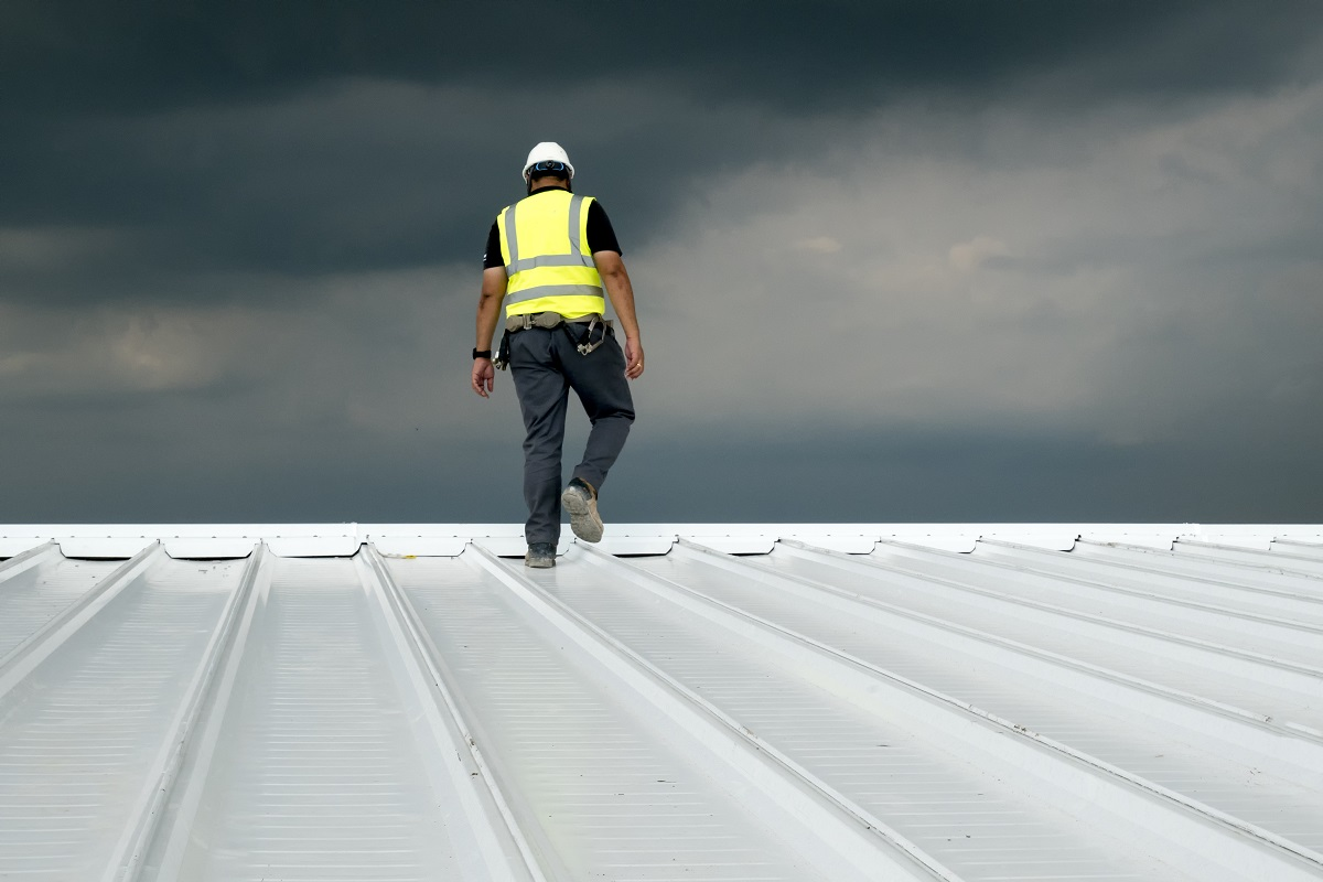 Worker Walking The Pitch On A Commercial Roof